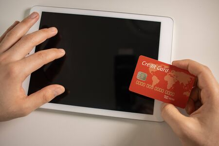 Photo pour man shopping using tablet pc and credit card .indoor.close-up - image libre de droit