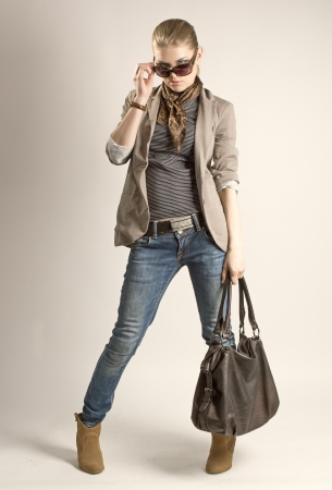 Fashionable shopping girl  Sexy blond Caucasian female in sunglasses holding leather bag