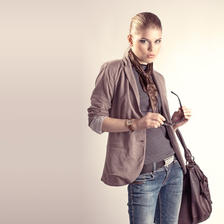 Beautiful fashion studio portrait of pretty blond Caucasian woman holding sunglasses with big leather bag  Young sexy girl with professional makeup