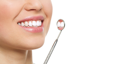 Dental care and inspection. Close-up of woman healthy white smile with mirror. Dentist visit concept.