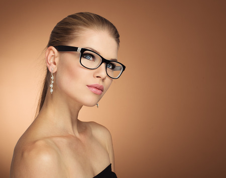 Photo pour Fashion portrait of young glamour female in optical eyewear with black frame over golden background. Pretty girl with beautiful evening makeup wearing jewelery posing in studio. - image libre de droit