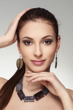 Photo pour Close-up portrait of young stylish Caucasian brunette girl wearing massive jewelery. - image libre de droit
