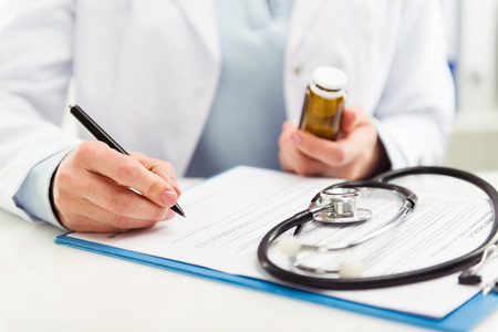 Photo pour Female doctor filling medical form on clipboard holding ballpoint and medicine bottle. Healthcare and insurance concept. - image libre de droit