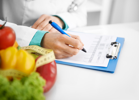 Photo pour Doctor nutritionist writing case history in the office. Young woman dietitian prescribing recipe. - image libre de droit
