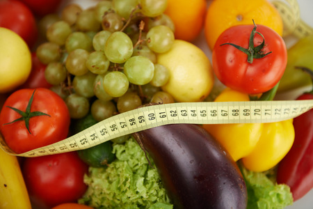 Slim down concept. Close-up of measuring tape lying on fresh and healthy fruits and vegetables.