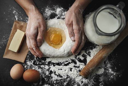Woman hands kneading dough on the black board with eggs, milk, butter and flour. Healthy breakfast preparation concept.
