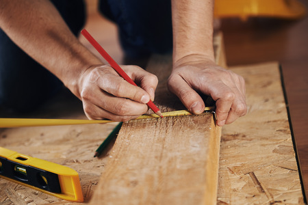 Photo pour Craftsman measuring wooden plank with ruler on the floor. Concept of diy, woodworking and home renovation. - image libre de droit
