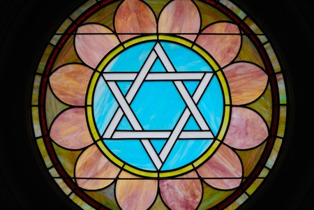 Colorful stain glass image of a Star of David in a synagogue.
