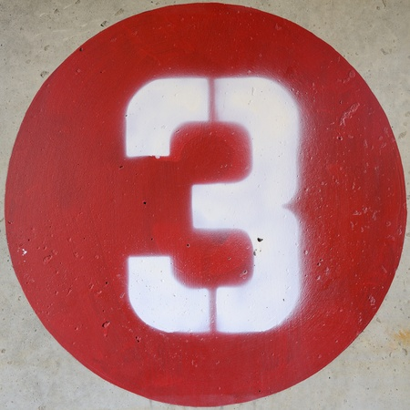 number 3 in a red circle on a concrete wall