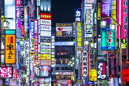 TOKYO, JAPAN - MARCH 14, 2014: Signs densely line an alleyway in Kabuki-cho. The area is a renown nightlife and red-light district.
