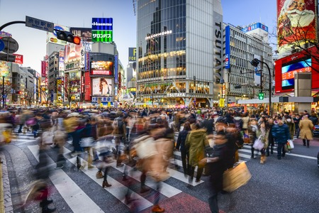 TOKYO, JAPAN - DECEMBER 14, 2012: Pedestrians walk at Shibuya Crossing. The scrambe crosswalk is one of the largest in the world.