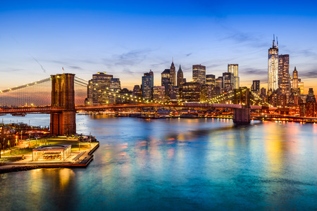 New York City, USA skyline over East River and Brooklyn Bridge.