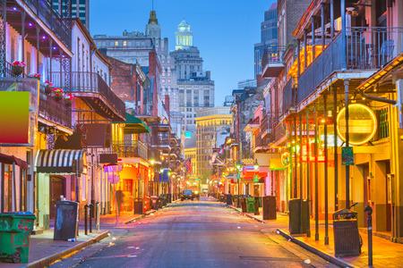 Bourbon St, New Orleans, Louisiana, USA cityscape of bars and restaurants at twilight.