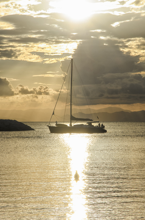 View of sailing boat crossing the sun glitter