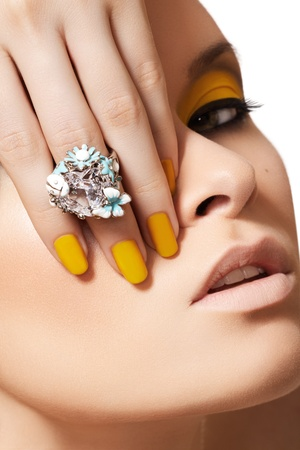 Foto de Close-up portrait of beautiful model face with neon yellow fashion make-up and with big crystal ring. Disco makeup and manicure, bright nail polish  - Imagen libre de derechos