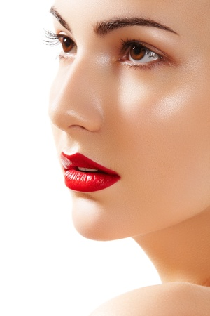 Close-up portrait of beautiful woman's purity face with bright red lips make-up. Cute model with clean shiny skin