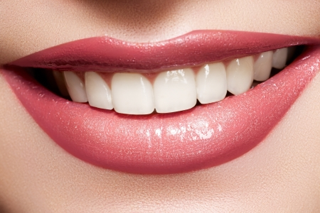 Close-up happy female smile with healthy white teeth, bright gloss lips make-up. Cosmetology, dental and beauty care