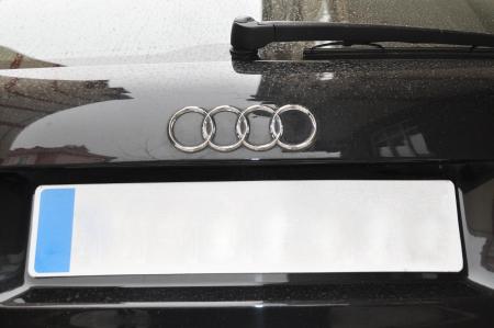 Audi logo on a wet black car