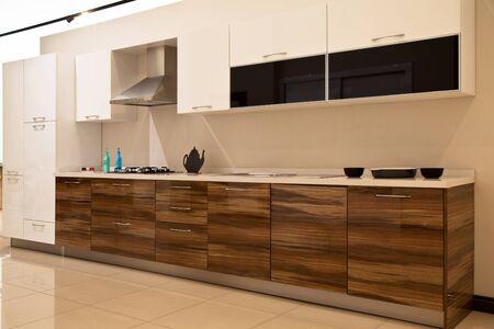 Foto de Interior of luxurious modern kitchen equipment and walnut white cabinets - Imagen libre de derechos