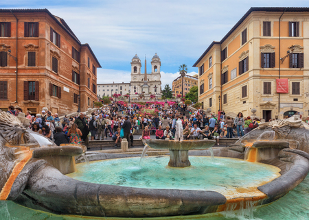Rome, Italy - May 2, 2011: Spanish steps and Ugly Boat fountain surronded by hundreds of tourists with Trinita dei Monti church on background
