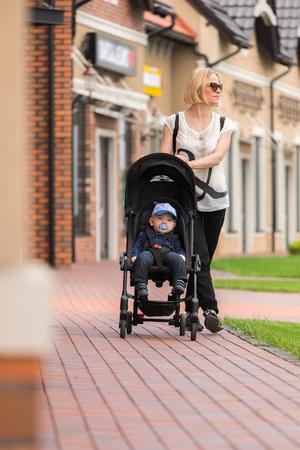 Photo pour A young mother takes her son in a stroller along shop windows in an outdoor mall - image libre de droit