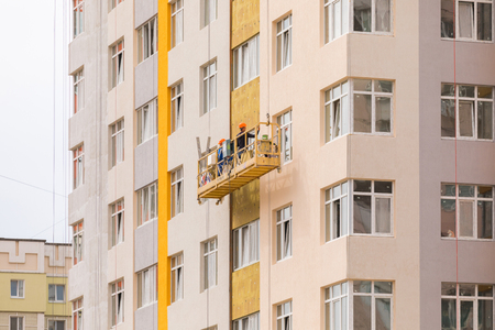 Foto de Builders paint the facade of a high-rise residential building - Imagen libre de derechos