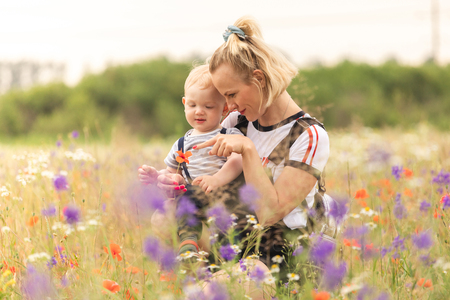 Photo pour Mother and child playing in the field with flowers. - image libre de droit