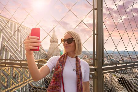Photo pour A woman takes a selfie picture on her phone on the roof of St. Stephens Cathedral in Vienna, Austria - image libre de droit