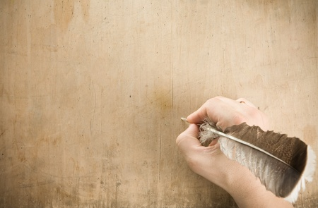 Photo pour writing hand with pen feather at old wood background texture - image libre de droit