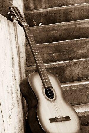 sepia image of guitar near steps