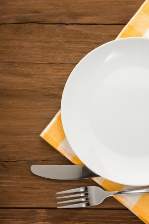 Photo pour plate, knife and fork at napkin on wooden background - image libre de droit