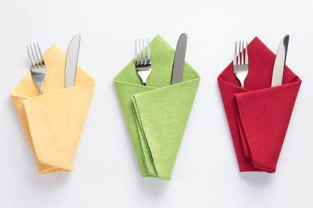 Foto de knife and fork in folded napkin at white background, top view - Imagen libre de derechos