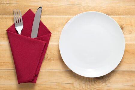 Photo pour plate, knife and fork at rustic wooden plank board table background, top view - image libre de droit