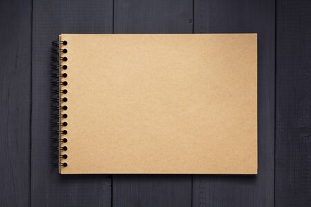 Photo for paper notebook at black wooden background surface table, top view - Royalty Free Image