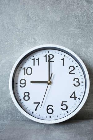 Foto de wall clock at grey shelf with abstract background surface - Imagen libre de derechos