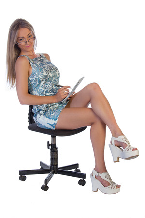 Young beautiful woman with long blond hair holding a note pad and pen, wearing glasses, sitting on a chair isolated on white background