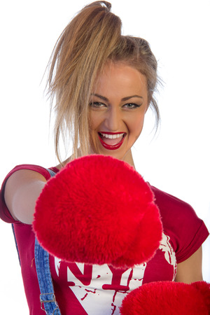 Extremely beautiful and sexy young adult caucasian woman playful with red ruf boxing gloves, isolated on white