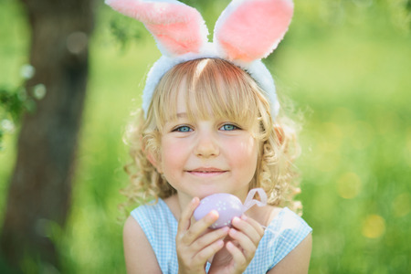 Photo pour Cute funny girl with Easter eggs and bunny ears at garden. easter concept. Laughing child at Easter egg hunt. Child in park with eggs, spring concept - image libre de droit