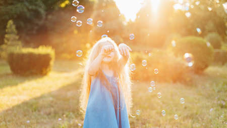Photo pour Child whirling, dancing plays on the meadow. Girl having fun with bubbles. Cute little longhair blonde girl dancing with soap bubbles at sunset park. - image libre de droit