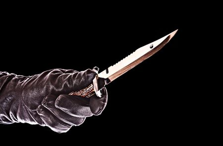 knife in black glove isolated on black