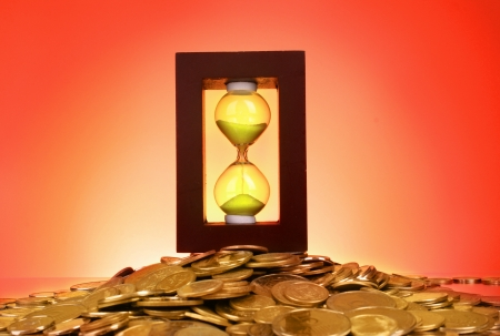 Hourglass and coins on red background