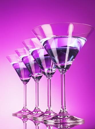 Four martini glasses on purple background
