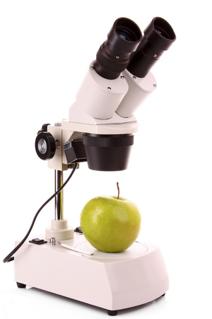 Green apple and microscope isolated on white