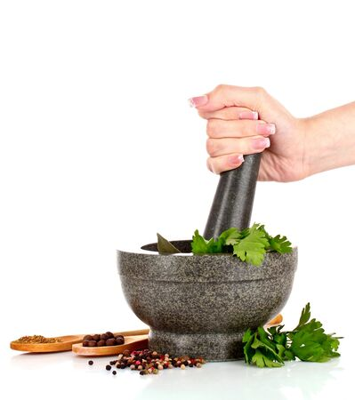 Mortar and pestle, parsley and pepper isolated on white