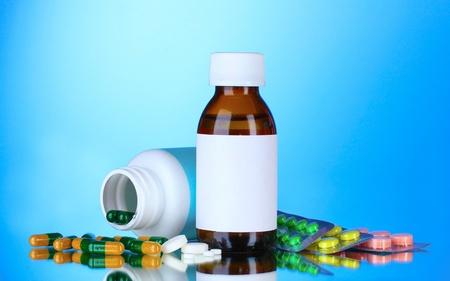 Medical bottles and pills on blue background