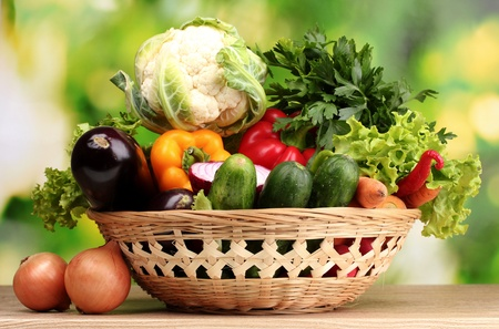 Fresh vegetables in basket on  wooden table on green backgroundの写真素材