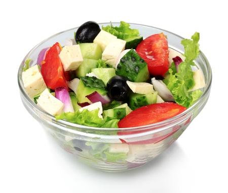 Foto de Tasty greek salad in transparent bowl isolated on white - Imagen libre de derechos