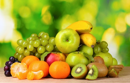 Foto de Ripe juicy fruits on wooden table on green background - Imagen libre de derechos