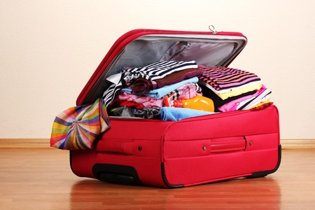 Open red suitcase with clothing in the room