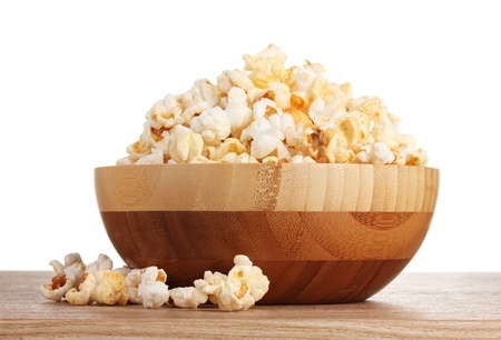 popcorn in wooden bowl on wooden table on white background